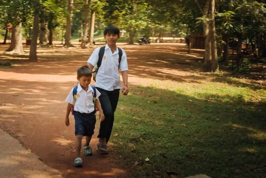 2019-11-15 / Siem Reap, Cambodia - Two boys in school uniform walk down a dirt road in a rural area.