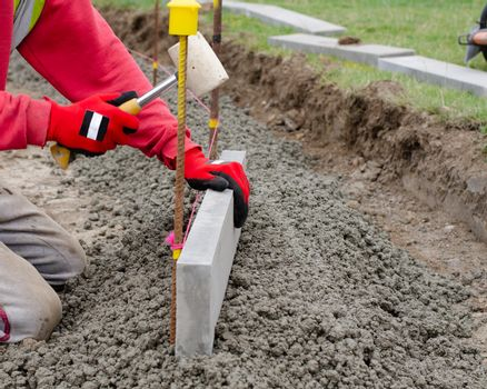 Laing edging kerb on semidry concrete during roadworks and new footpath construction  by groundworker wearing safety gloves