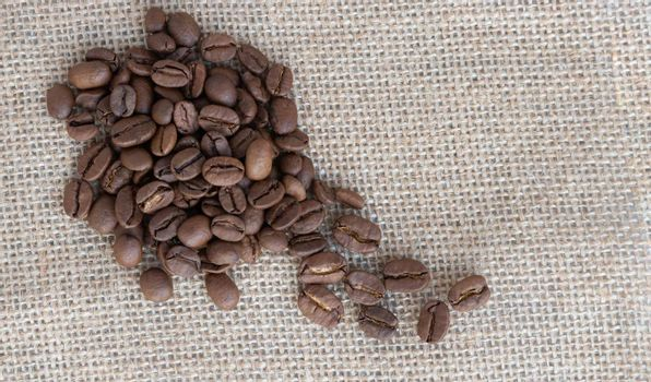 Coffee beans lie against a background of burlap. Space for text.
