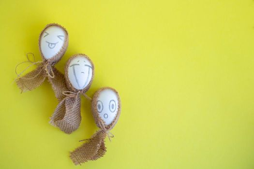 Three white eggs with funny faces in sackcloth on a yellow background. Easter Concept. Space for text.