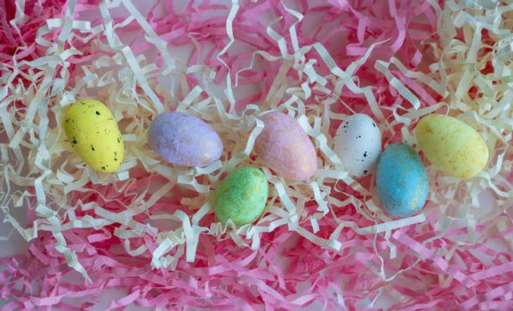 Colorful eggs on a background of pink and white paper tinsel. Easter concept.