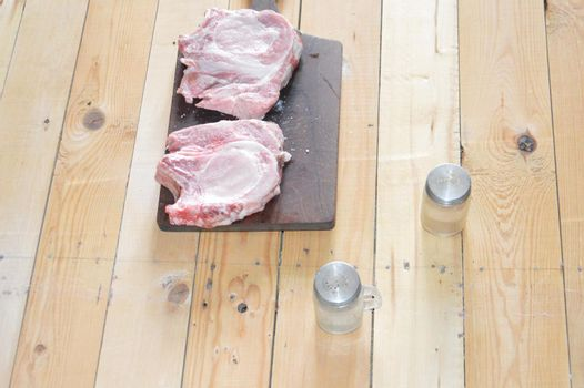 Salted and peppery steak lies on a the wooden stand