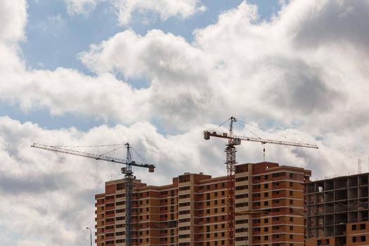 building process of large residential apartment building with crane on cloudy sky background.