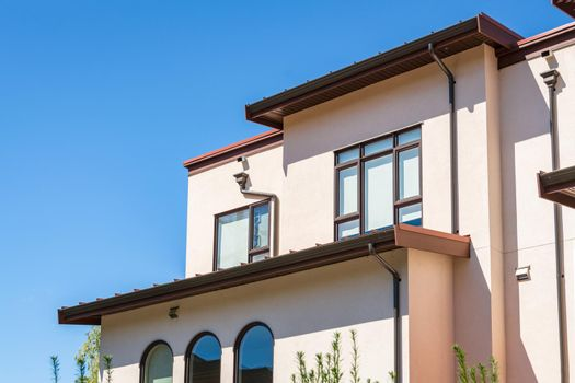 Top of residential townhouse on blue sky background