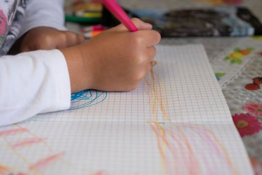 Happy child draws fairy-tale character with felt-tip pens on paper.