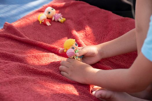 Cute girl playing with her dolls on a sunbed on a sandy beach on a sunny day.