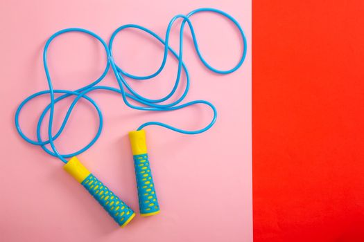 Minimalism fitness concept. Skipping rope on color background.