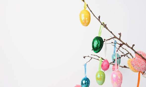 decorative sequin eggs hang on a branch on a white background, easter background