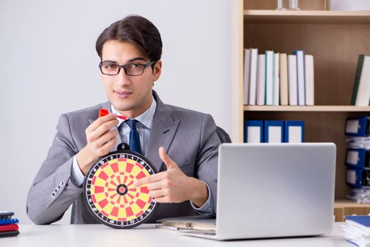 Businessman with dartboard sitting at the office