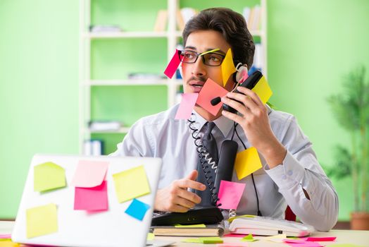 Young help desk operator working in office with many conflicting priorities
