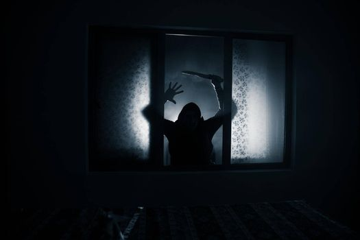 Silhouette of an unknown shadow figure on a door through a closed glass door. The silhouette of a human in front of a window at night. Scary scene halloween concept of blurred silhouette of maniac.
