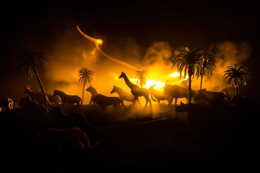 A group of animals are grouped together at foggy night with burning colorful background. Animals Running Escaping to Save Their Lives from fire. Selective focus.