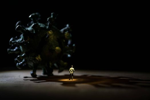 Corona virus global pandemic concept. Miniature man standing near big Corona virus novel in dark. Creative decoration with fog and backlight. Selective focus
