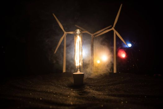 Electricity power in nature or clean energy concept. Wind Turbine producing alternative energy at night. Glowing bulb powered by alternative energy. Creative decoration with small miniature. Selective focus