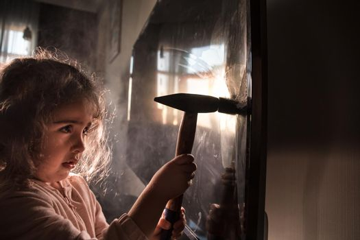 Cute little girl standing in front of a TV with broken screen holding a hammer. Home insurance concept. Child smashed led TV screen with a hammer