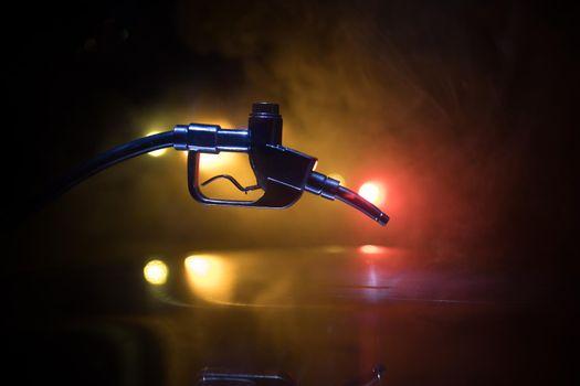 Creative concept. Silhouette of gasoline pistol miniature on dark toned foggy background. Fuel gun close up burning. Selective focus