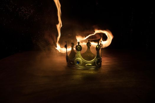 low key image of beautiful queen/king crown over wooden table. vintage filtered. fantasy medieval period. Selective focus. Colorful backlight