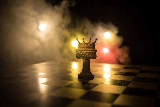 Beautiful queen/king crown on chessboard. chess board game concept of business ideas and competition and strategy ideas concept. Chess figures on a dark background with smoke and fog. Selective focus