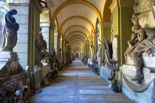 GENOA, ITALY - June 2020: corridor with statues - beginning 1800 - in a Christian Catholic cemetery - Italy