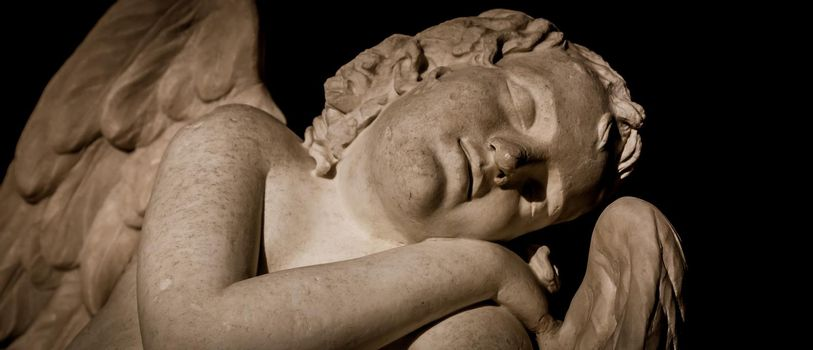 MILAN, ITALY - CIRCA AUGUST 2020: Cute sleeping angel. Statue made in marble, end of 18th century, unknown sculptor. Concept for sleep, innocence and newborrn.