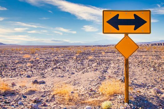 Directional sign in the desert with scenic blue sky and wide horizon. Concept for trip, freedom, holiday and transportation.