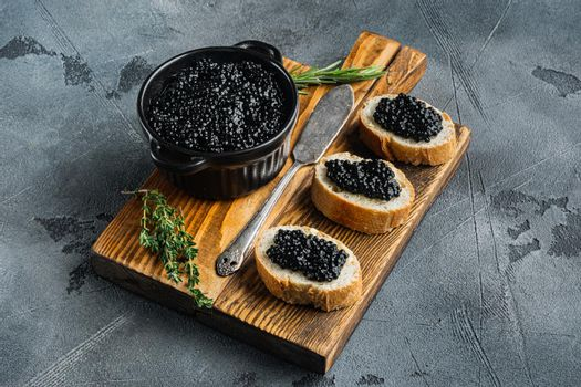 Sandwiches with black caviar, on gray background