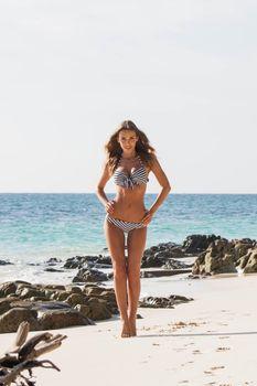Happy tanned girl in bikini at seaside, blue sea water in background