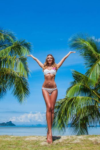 Portrait of young model woman in bikini raising her arms at tropical beach with palms in Thailand.