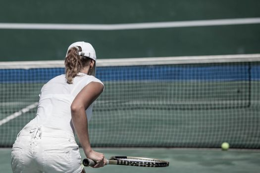 Back view of woman in white tennis uniform playing tennis on court