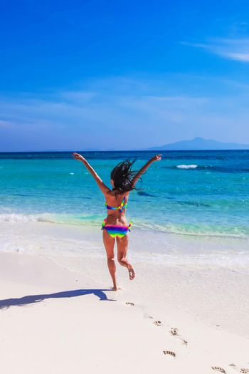 Beautiful happy girl running to tropical sea with arms raised