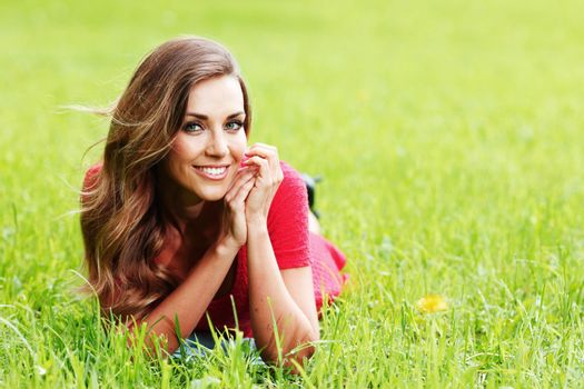 Smiling woman laying on spring green grass and smiling