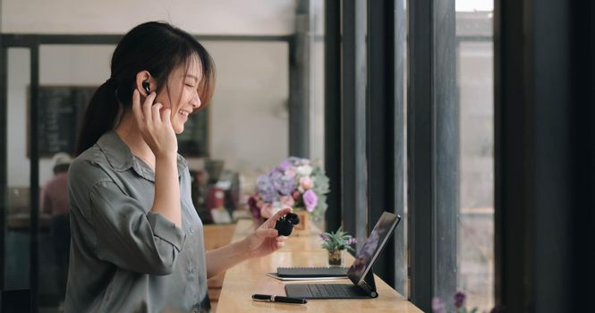 close up of asian young girl use wireless earbuds to have online language courses and searching information via laptop computer at cafe.