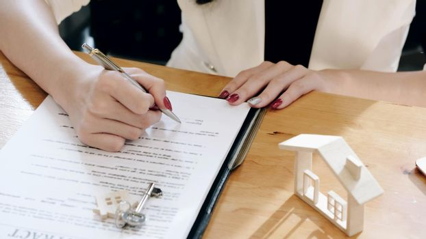 Real estate agents and client to agree buy a home and sign documents contract house with customer.