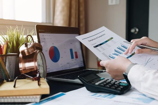 Business woman working with financial data hand using calculator for analysis financial data, Business financial and accounting concept.