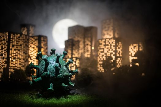 Cartoon style city buildings. Realistic city building miniatures with lights. Big Corona virus miniature in the city at night. Stay home stay safe or coronavirus pandemic concept. Selective focus.