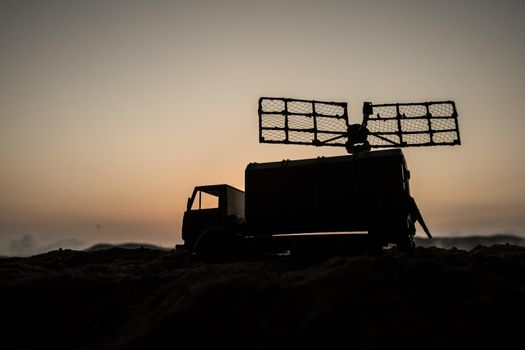 Creative artwork decoration. Silhouette of mobile air defence truck with radar antenna during sunset. Satellite dishes or radio antennas against evening sky. Selective focus