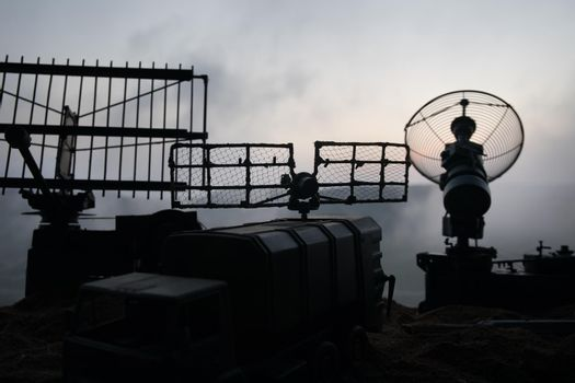 Creative artwork decoration. Silhouette of mobile air defence truck with radar antenna during sunset. Rocket launcher aimed at sky ready to attack. Selective focus
