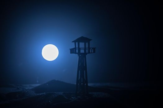 Creative artwork decoration. War concept. Silhouette of army watchtower at night. Selective focus