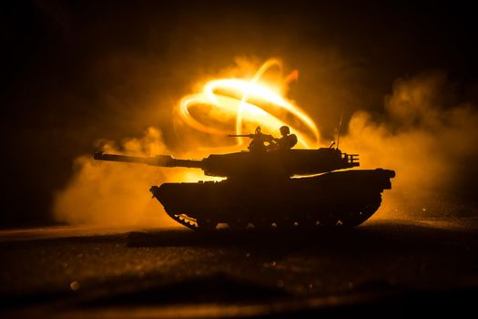War Concept. Armored vehicle silhouette fighting scene on war foggy sky background at night. American tank ready to fight. Creative decoration
