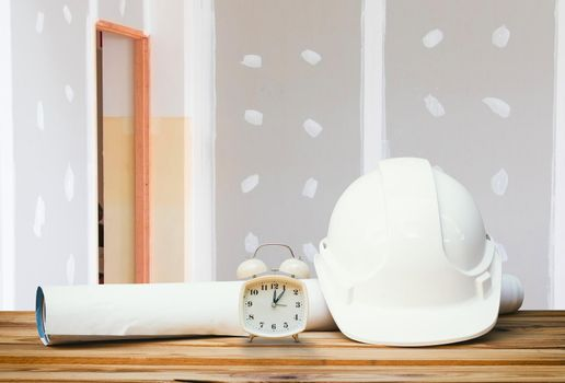 white safety helmet plastic, paper roll plan blueprint alarm clock time a rest at noon on wood floor table and gypsum board wall remodel interior with copy space add text