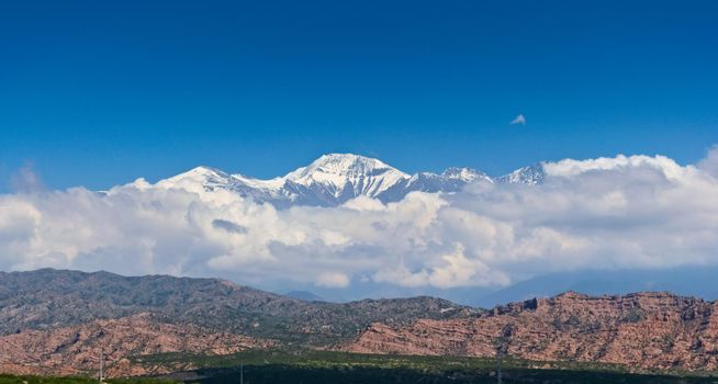 Scenic view of snow capped peak El Plata (6100 MSL) above the clouds, as seen from Lake Potrerillos, in Mendoza, Argentina.