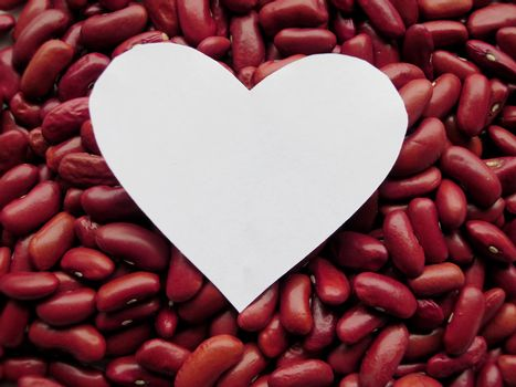 Closeup of White Heart shape on Raw Red Kidney Beans Background