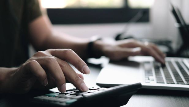 Close up Businessman using calculator and laptop for do math finance on wooden desk in office and business working background, tax, accounting, statistics and analytic research concept.