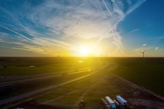Road Leading to view of the Texas wind turbine farms in the beautiful sky during sunset showing
