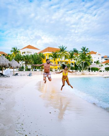 Tropical luxury resort Curacao with private beach and palm trees, luxury vacation Curacao Caribbean, happy young couple on the beach during vacation, mid age men and woman asian girl and european men