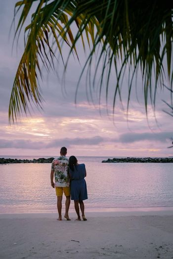 Tropical luxury resort Curacao with private beach and palm trees, luxury vacation Curacao Caribbean, couple men and woman watching sunset at the beach with pool and palm trees, mid age couple beach