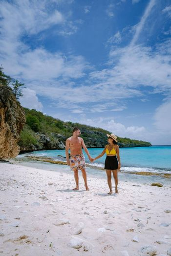 Aerial view of the coast of Curacao in the Caribbean Sea with turquoise water, white sandy beach, coral reef Playa Cas Abao Curacao, couple mid age european man and asian woman during vacation