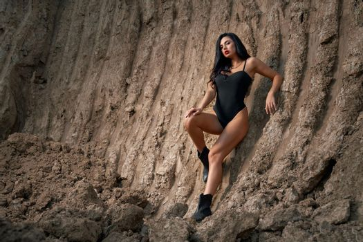 Gorgeous woman in black bodysuit standing among dry quarry