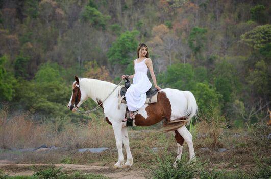 Women on skirt dress Riding Horses On field landscape Against Sky During Sunset