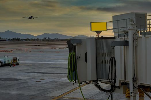 Sky Harbor airport airport at sunset with plane taking off on boarding bridge used to connect airport in the Phoenix, Arizona USA